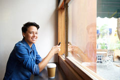 Smiling young woman with cell phone at cafe Stock Photography