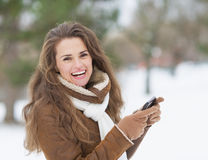 Smiling young woman with cell phone in winter outdoors Stock Images