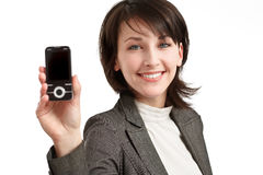 Smiling young woman with cellphone in hand Royalty Free Stock Images