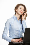Smiling young woman with cellphone and laptop Stock Photo