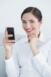 Smiling young woman with cellphone on sofa Stock Photos