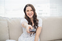 Smiling young woman changing tv station Stock Photos