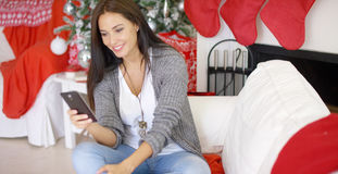 Smiling young woman checking Christmas messages. On her mobile phone from friends and family in a decorated festive home Royalty Free Stock Photo