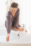 Smiling young woman checking water temperature in bathtub Royalty Free Stock Images
