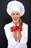 Smiling young woman chef with tomatos juggle Royalty Free Stock Photos
