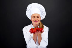 Smiling young woman chef with tomatos juggle Stock Image