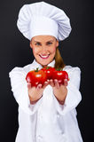 Smiling young woman chef with tomatos juggle. Portrait of young woman chef with tomatos juggle Stock Images