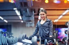 Smiling young woman choosing dumbbells in gym Royalty Free Stock Photo
