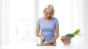 Smiling young woman chopping celery at home stock footage