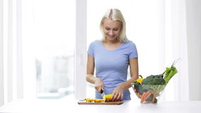 Smiling young woman chopping squash at home stock video