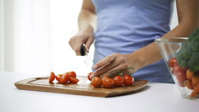 Smiling young woman chopping tomatoes at home stock footage
