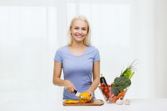 Smiling young woman chopping vegetables at home. Healthy eating, vegetarian food, cooking, dieting and people concept - smiling young woman chopping vegetables Stock Images