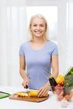 Smiling young woman chopping vegetables at home. Healthy eating, vegetarian food, cooking , dieting and people concept - smiling young woman chopping vegetables Stock Images
