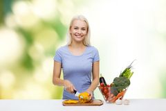 Smiling young woman chopping vegetables at home. Healthy eating, vegetarian food, cooking, dieting and people concept - smiling young woman chopping vegetables Stock Photography