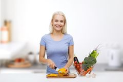 Smiling young woman chopping vegetables on kitchen. Healthy eating, vegetarian food, cooking, dieting and people concept - smiling young woman chopping Royalty Free Stock Image