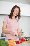 Smiling young woman chopping vegetables in kitchen Stock Photography