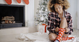 Smiling young woman in a Christmas living room Stock Photo