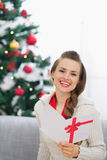 Smiling young woman with Christmas postcard Royalty Free Stock Images