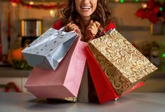 Woman with christmas shopping bags in christmas de. Smiling young woman with christmas shopping bags in christmas decorated kitchen royalty free stock image