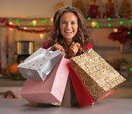 Smiling young woman with christmas shopping bags in kitchen Stock Photos