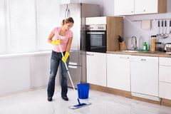 Young Woman Cleaning Kitchen Floor With Mop. Smiling Young Woman Cleaning Kitchen Floor With Mop In Kitchen At Home stock photos