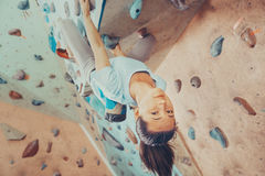 Smiling young woman climbing indoor Stock Images