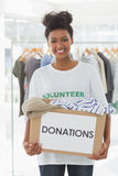 Smiling young woman with clothes donation Royalty Free Stock Images