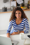 Smiling young woman with coffee cup and laptop in Royalty Free Stock Images