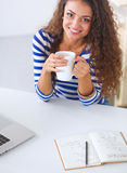 Smiling young woman with coffee cup and laptop in Stock Photography