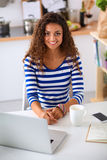 Smiling young woman with coffee cup and laptop in Stock Images