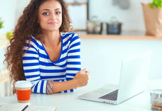 Smiling young woman with coffee cup and laptop in the kitchen at home Royalty Free Stock Photography