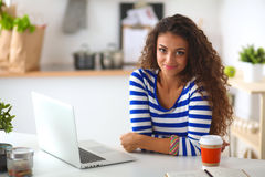 Smiling young woman with coffee cup and laptop in the kitchen at home Royalty Free Stock Photo