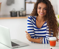 Smiling young woman with coffee cup and laptop in the kitchen at home Royalty Free Stock Photos