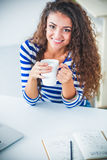 Smiling young woman with coffee cup and laptop in the kitchen at home Royalty Free Stock Images