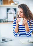 Smiling young woman with coffee cup and laptop in the kitchen at home Royalty Free Stock Image