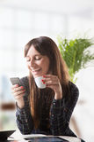 Smiling young woman with a coffee and send a message Stock Image