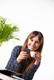 Smiling young woman with a coffee and subject a phone Royalty Free Stock Image
