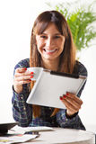 Smiling young woman with a coffee and subject a tablet royalty free stock images