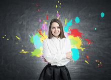Smiling young woman and color splashes Royalty Free Stock Photography