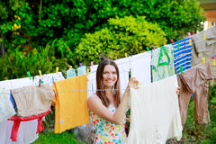 Smiling young woman in colorful dress hanging laundry on clothesline at the backyard Stock Photo