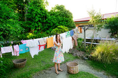 Smiling young woman in colorful dress hanging laundry on clothesline at the backyard Royalty Free Stock Images