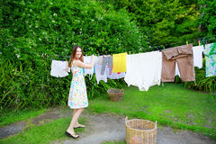 Smiling young woman in colorful dress hanging laundry on clothesline at the backyard Stock Photography
