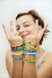 Smiling young woman with colorful rubber bracelets on her hands стоковое изображение