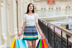 Smiling young woman with the colourful shopping bags from the fancy shops. Stock Photo