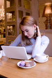 Smiling young woman with computer at breacfast. Smiling blonde young woman at the table with a cup of tea at the computer in cafe Stock Image