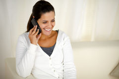 Smiling young woman conversing on cellphone Stock Image