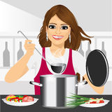 Smiling young woman cooking in kitchen Stock Photography