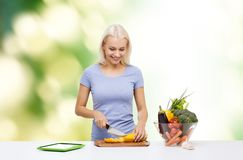 Smiling young woman cooking vegetables Royalty Free Stock Image