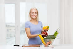 Smiling young woman cooking vegetables at home Stock Photography