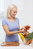 Smiling young woman cooking vegetables at home Stock Images